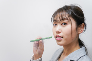 電子タバコを吸う若いビジネスウーマンの写真素材 [FYI04713847]