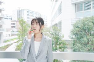 電子タバコを吸う若いビジネスウーマンの写真素材 [FYI04713852]