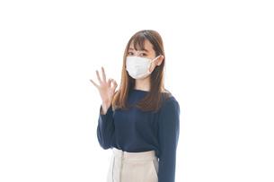 マスクを装着してOKサインをする若い女性の写真素材 [FYI04713884]