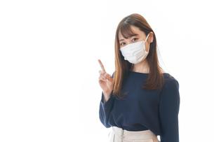 マスクを装着して指を指す若い女性の写真素材 [FYI04713890]