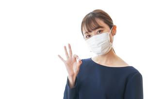 マスクを装着してOKサインをする若い女性の写真素材 [FYI04713908]