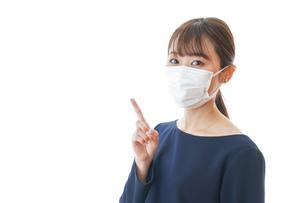 マスクを装着して指を指す若い女性の写真素材 [FYI04713910]
