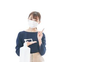 OKサインをしながらアルコール消毒をする若い女性の写真素材 [FYI04713937]
