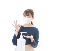 マスクを装着してOKサインをする若い女性の写真素材 [FYI04713943]
