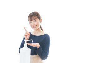 OKサインをしながらアルコール消毒をする若い女性の写真素材 [FYI04713964]