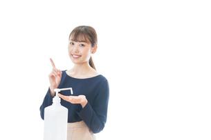 OKサインをしながらアルコール消毒をする若い女性の写真素材 [FYI04713965]