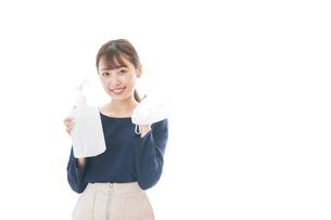 マスクとアルコール消毒液を持つ若い女性の写真素材 [FYI04713994]