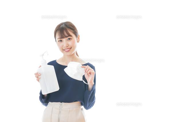 マスクとアルコール消毒液を持つ若い女性の写真素材 [FYI04714010]