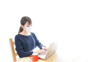 マスクをしてリモートワークをする若いビジネスウーマンの写真素材 [FYI04714067]
