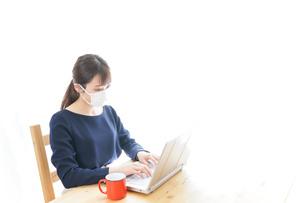 マスクをしてリモートワークをする若いビジネスウーマンの写真素材 [FYI04714070]