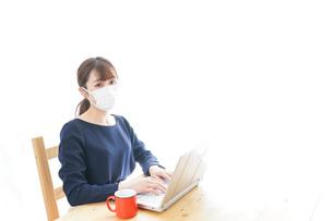 マスクをしてリモートワークをする若いビジネスウーマンの写真素材 [FYI04714073]