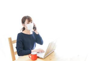マスクをしてリモートワークをする若いビジネスウーマンの写真素材 [FYI04714076]