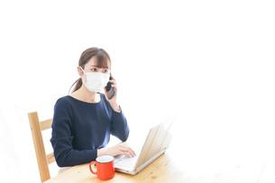 マスクをしてリモートワークをする若いビジネスウーマンの写真素材 [FYI04714080]