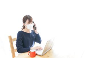 マスクをしてリモートワークをする若いビジネスウーマンの写真素材 [FYI04714082]