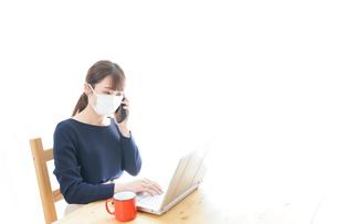 マスクをしてリモートワークをする若いビジネスウーマンの写真素材 [FYI04714084]