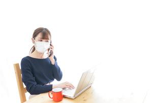 マスクをしてリモートワークをする若いビジネスウーマンの写真素材 [FYI04714091]