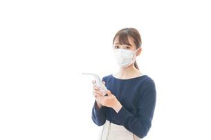 体温の測定をする若いビジネスウーマンの写真素材 [FYI04714112]