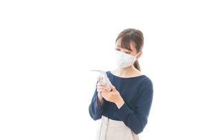 体温の測定をする若いビジネスウーマンの写真素材 [FYI04714114]
