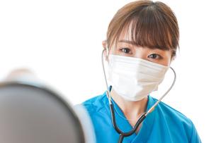 マスクを装着して診療をする医師の写真素材 [FYI04714266]