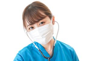 マスクを装着して診療をする医師の写真素材 [FYI04714275]