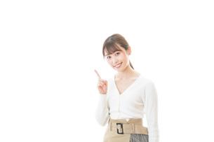 笑顔で指をさす若い女性の写真素材 [FYI04714350]