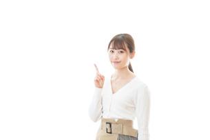 笑顔で指をさす若い女性の写真素材 [FYI04714353]