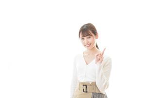 笑顔で指をさす若い女性の写真素材 [FYI04714354]