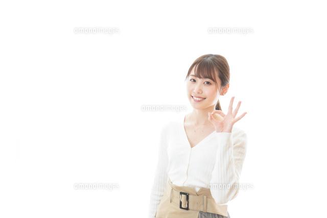 笑顔でOKサインを示す若い女性の写真素材 [FYI04714359]