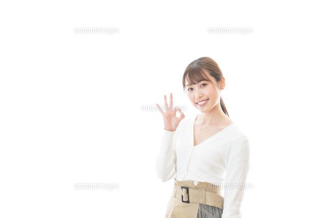 笑顔でOKサインを示す若い女性の写真素材 [FYI04714368]