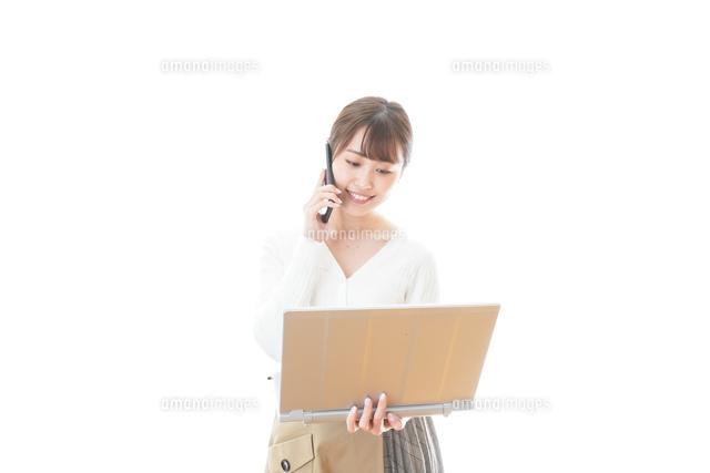 笑顔で在宅勤務をする若い女性の写真素材 [FYI04714381]