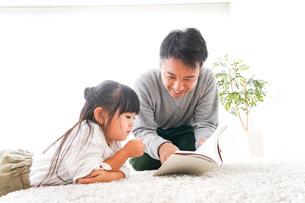 本の読み聞かせをするお父さんの写真素材 [FYI04714443]