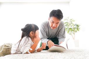 本の読み聞かせをするお父さんの写真素材 [FYI04714446]
