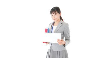 オフィスで書類を確認する若いビジネスウーマンの写真素材 [FYI04714545]