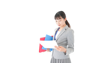 オフィスで書類を確認する若いビジネスウーマンの写真素材 [FYI04714559]