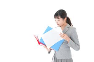 オフィスで書類を確認する若いビジネスウーマンの写真素材 [FYI04714561]