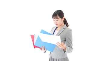 オフィスで書類を確認する若いビジネスウーマンの写真素材 [FYI04714563]