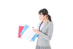 オフィスで書類を確認する若いビジネスウーマンの写真素材 [FYI04714564]