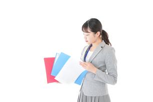 オフィスで書類を確認する若いビジネスウーマンの写真素材 [FYI04714565]