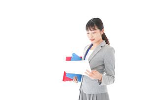 オフィスで書類を確認する若いビジネスウーマンの写真素材 [FYI04714566]