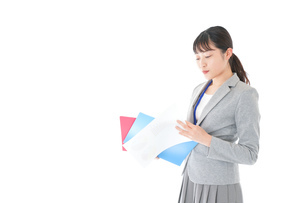 オフィスで書類を確認する若いビジネスウーマンの写真素材 [FYI04714568]