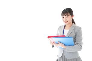 オフィスで書類を確認する若いビジネスウーマンの写真素材 [FYI04714570]