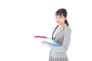 オフィスでファイルを持つ若いビジネスウーマンの写真素材 [FYI04714578]