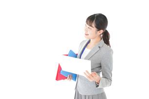 オフィスで書類を確認する若いビジネスウーマンの写真素材 [FYI04714581]