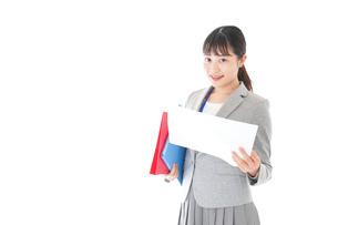 オフィスで書類を確認する若いビジネスウーマンの写真素材 [FYI04714582]