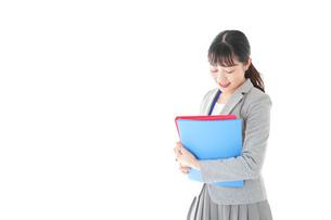 オフィスで書類を確認する若いビジネスウーマンの写真素材 [FYI04714590]
