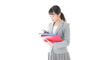 オフィスでスマートフォンを使う若いビジネスウーマンの写真素材 [FYI04714614]