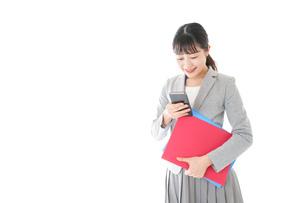 オフィスでスマートフォンを使う若いビジネスウーマンの写真素材 [FYI04714617]