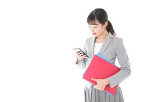 オフィスでスマートフォンを使う若いビジネスウーマンの写真素材 [FYI04714623]