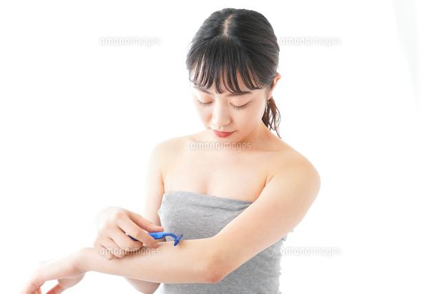 肌の脱毛をする若い女性の写真素材 [FYI04714929]
