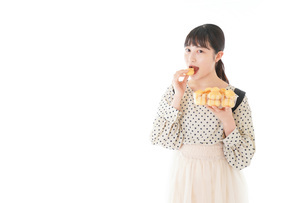 おやつを食べる若い女性の写真素材 [FYI04715145]
